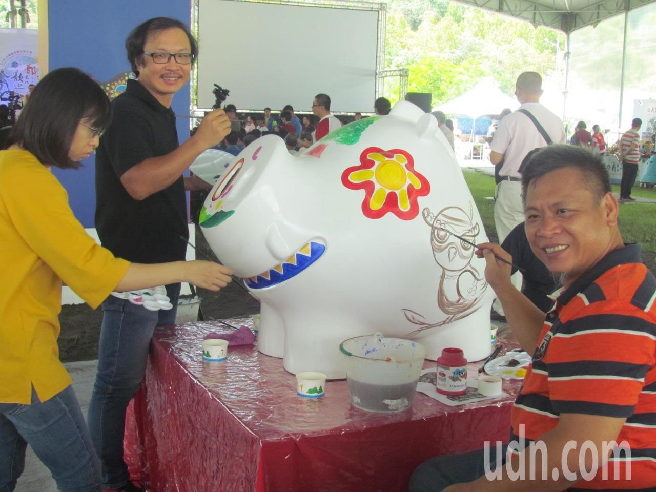 張立曄(左二)等畫家,在洪易老師製作的「山中明豬」身上彩繪。記者張家樂/攝影