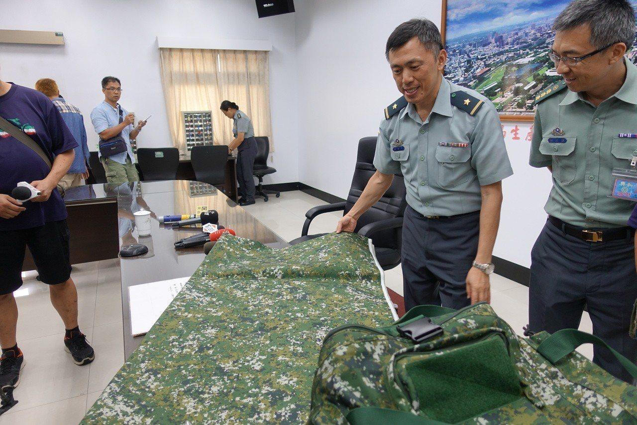國防部軍備局生產製造中心少將主任羅意中(右二)說明數位迷彩布料原料,製作攜行袋。...