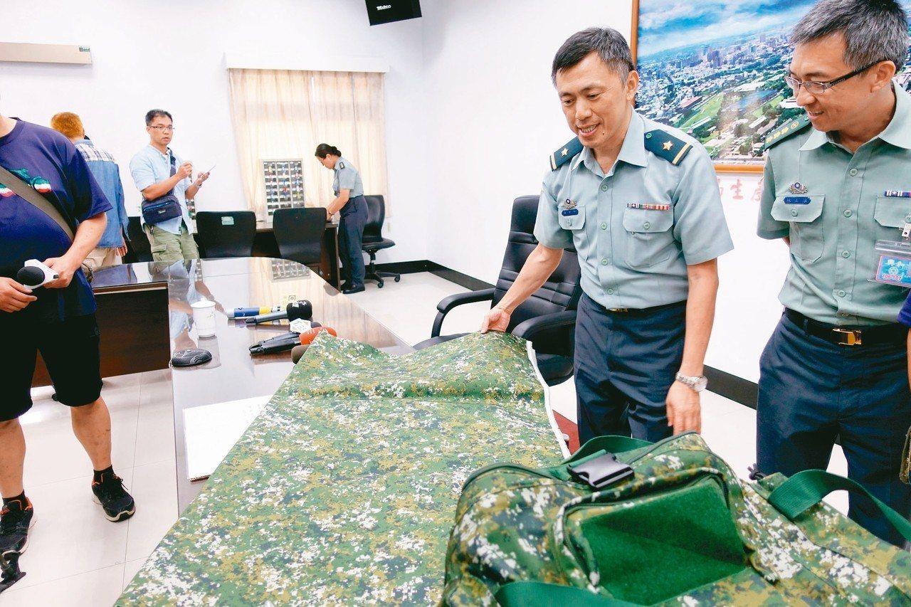 國防部軍備局生產製造中心少將主任羅意中(右二)說明,這批數位迷彩布料用於製作攜行...