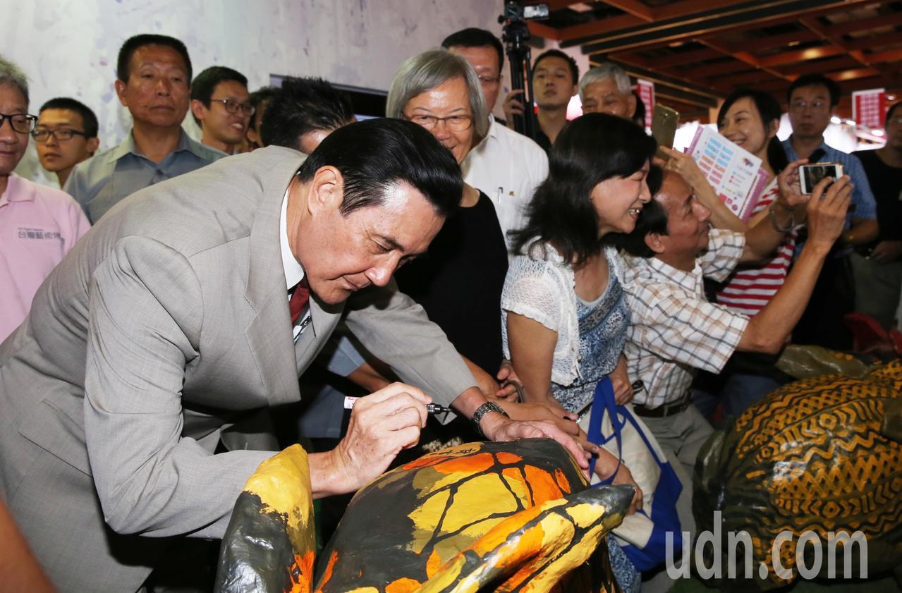馬英九受邀在展出的藝術作品上簽名。記者徐兆玄/攝影