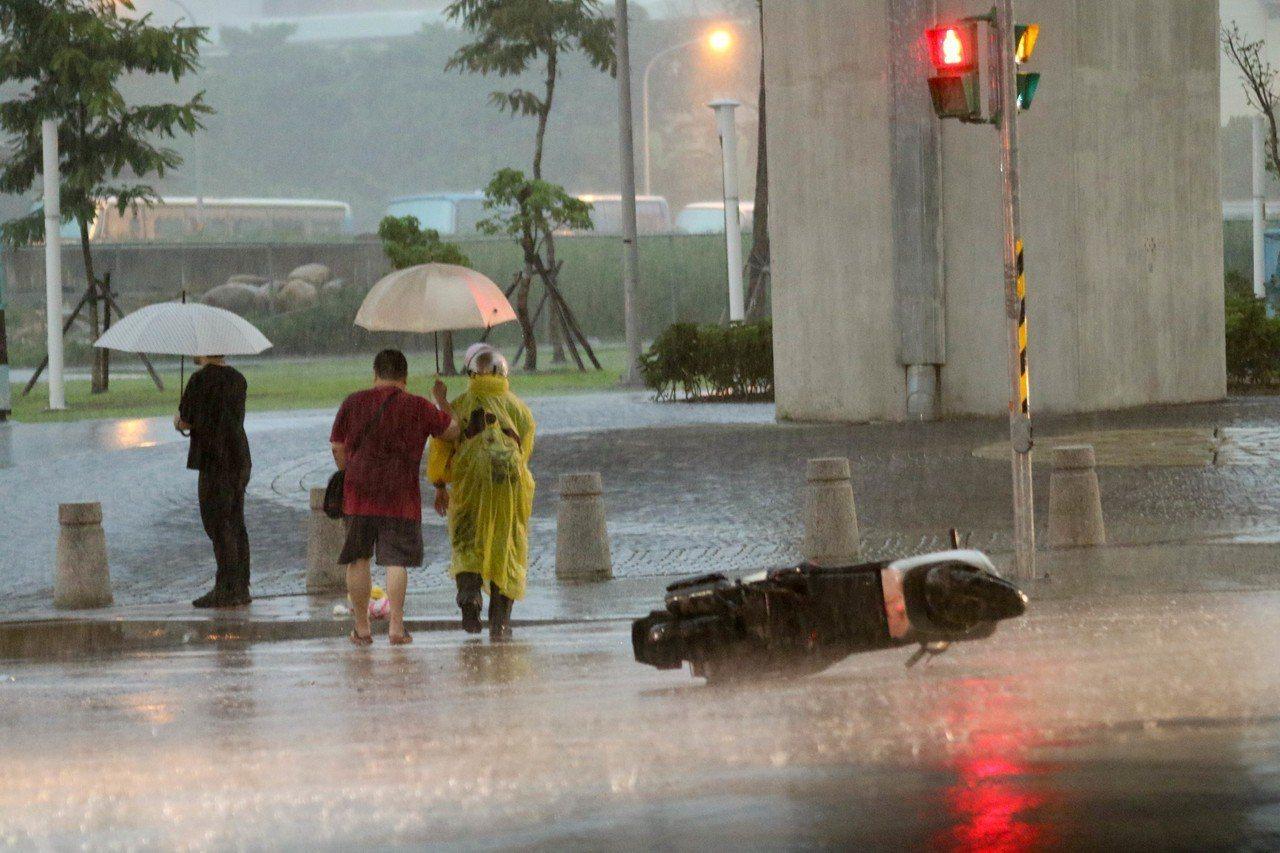 新北五股豪大雨機車騎士摔車,機車倒在大馬路上,豪大雨導致騎士無法將機車牽離。記者...