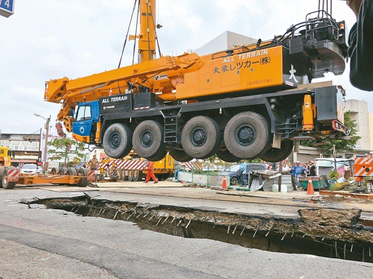 台南市昨天調動兩部大型重機械進場作業,將深陷天坑的百噸吊車吊起。 記者邵心杰/攝...