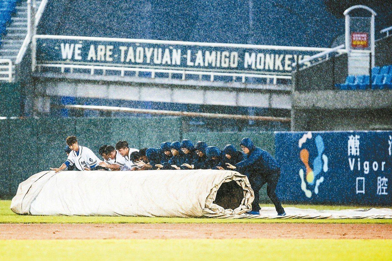 球賽進行到三局上半因雨勢過大比賽暫停,場務人員拉起帆布擋雨。 記者王騰毅/攝影