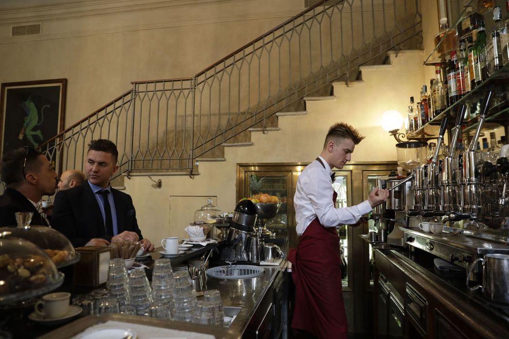 義大利米蘭一間傳統咖啡館,客人習慣站在吧檯旁很快喝完一杯濃縮咖啡。 (美聯社)