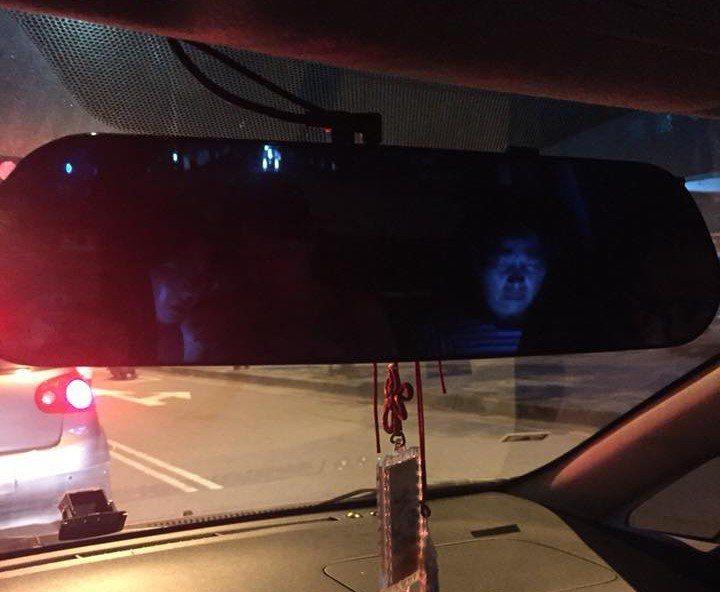 一位民眾開車載家人外出,但他從後視鏡看到後座的丈母娘低頭滑手機,手機藍光照在丈母...