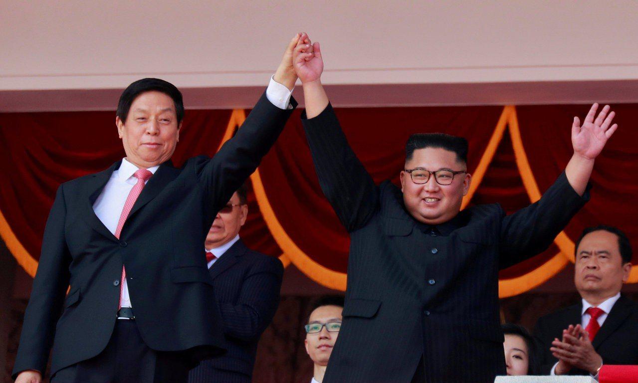 北韓領導人金正恩(右)9日在國慶閱兵的觀禮台上,舉起中國特使栗戰書的手。路透