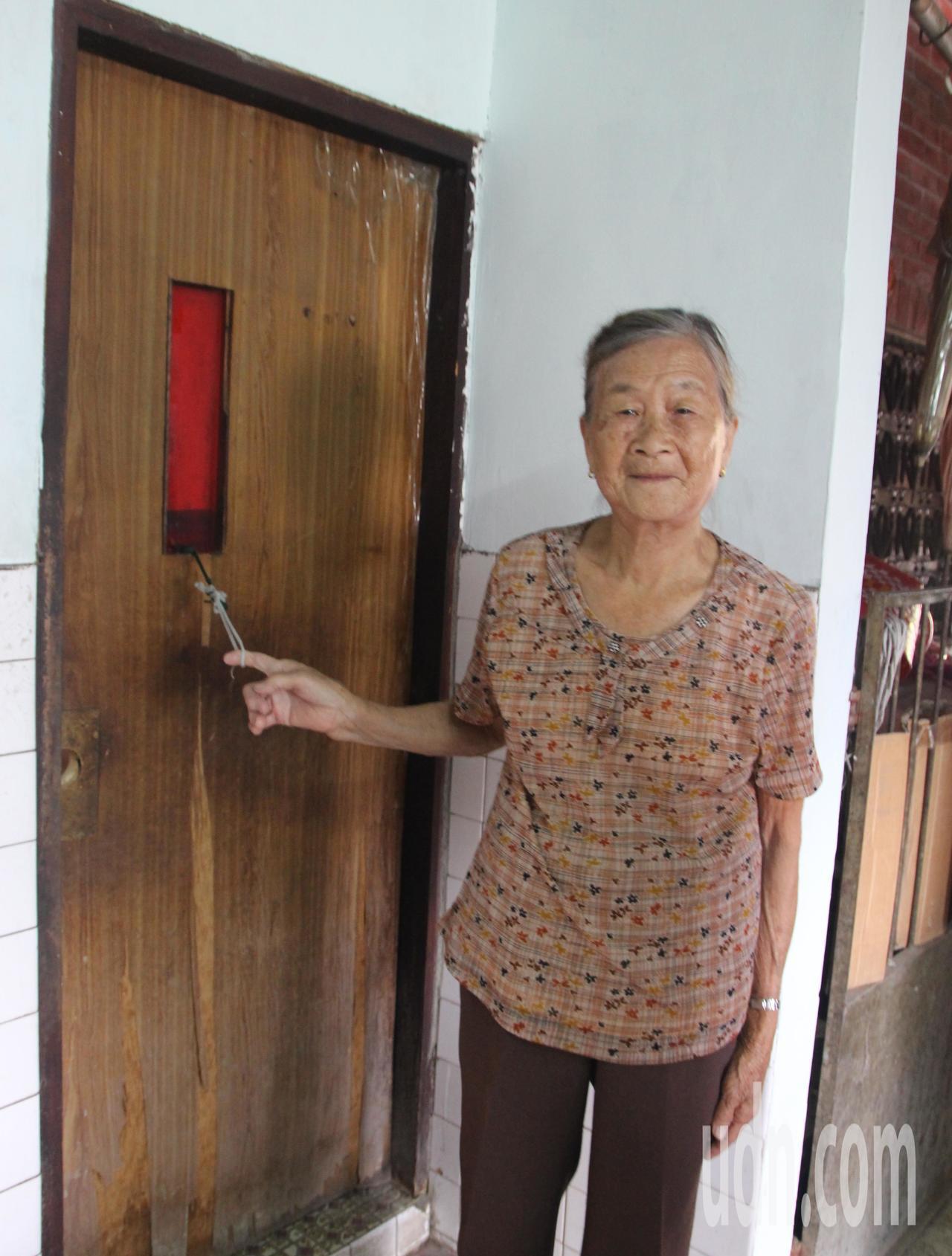 86歲秀英阿嬤廁所木門損壞了,拿棉線綁成圓環當拉門。記者林敬家/攝影