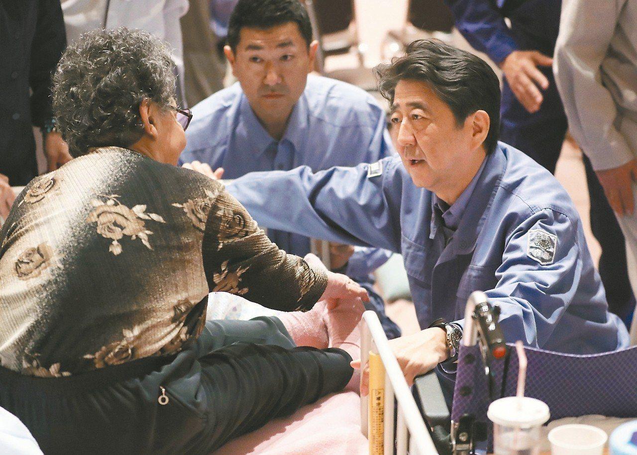 日相安倍晉三(右)九日到北海道安平町避難所慰問災民。 美聯社