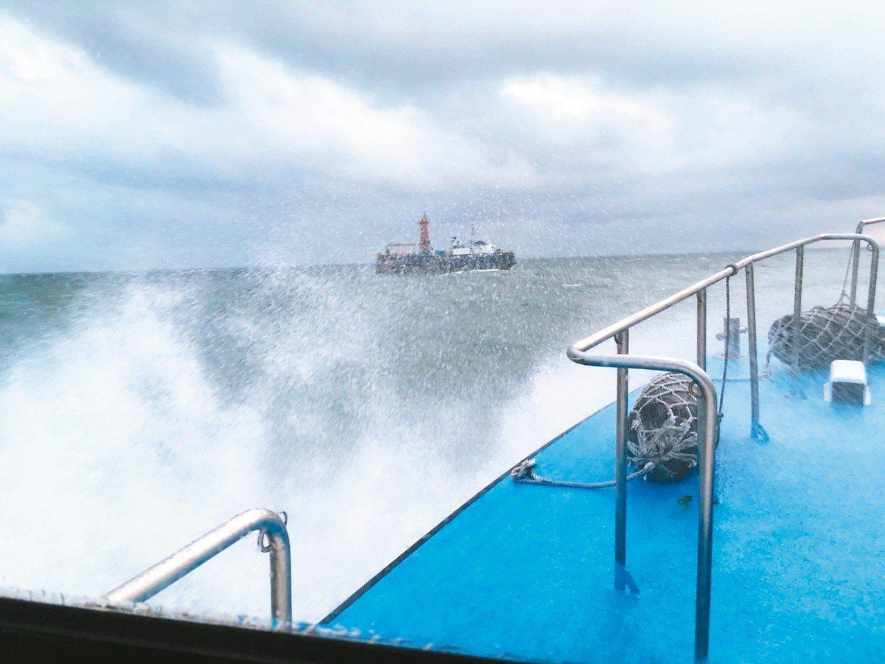 海巡署巡防艇冒著大浪,前進故障的工作船,驚險救人。 記者謝恩得/翻攝