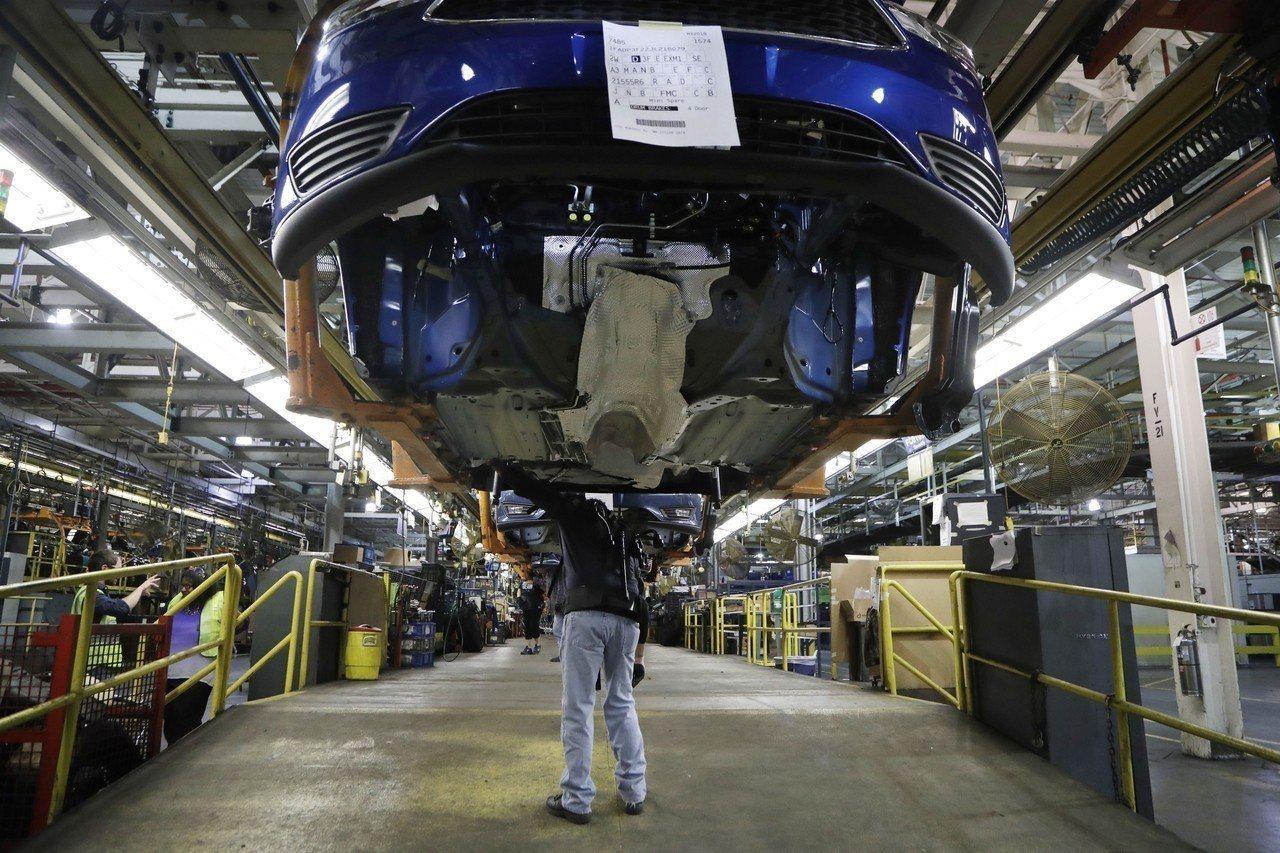 美國汽車福特在密西根州韋恩郡車廠的生產線員工正在組裝查看一台Focus車。美聯社
