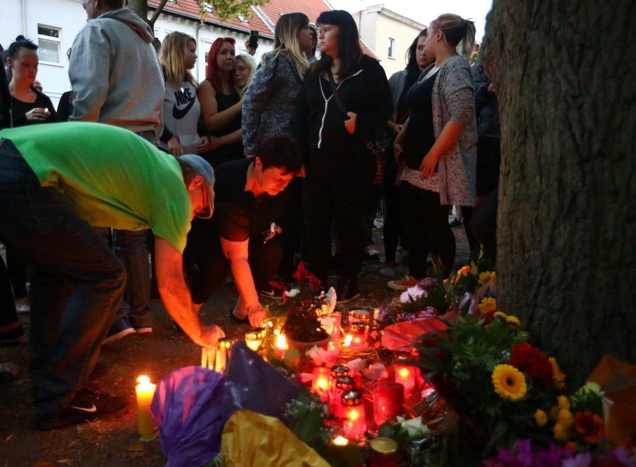 民眾紛紛獻花並點上蠟燭。路透