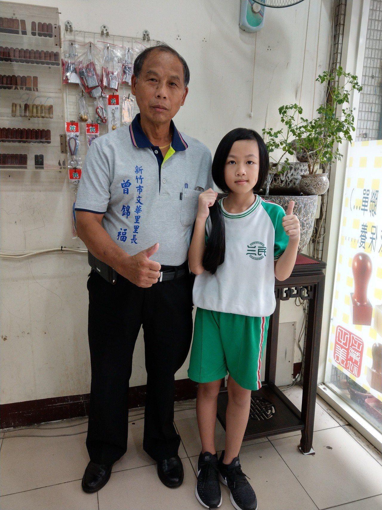 新竹市三民國小5年級學生彭一倢(從母姓,右)捐出秀髮,文華里長曾錦福(左)稱讚她...