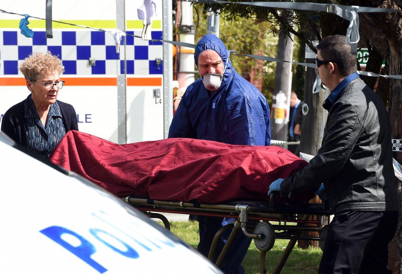 法醫等人10日從殺人現場移走屍體。(法新社)