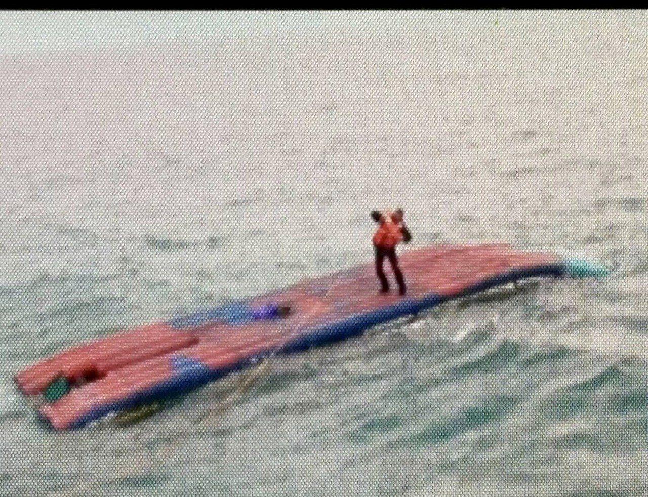 台南安平沿海今天風浪大,何姓船長站在翻覆管筏上待援。記者黃宣翰/翻攝