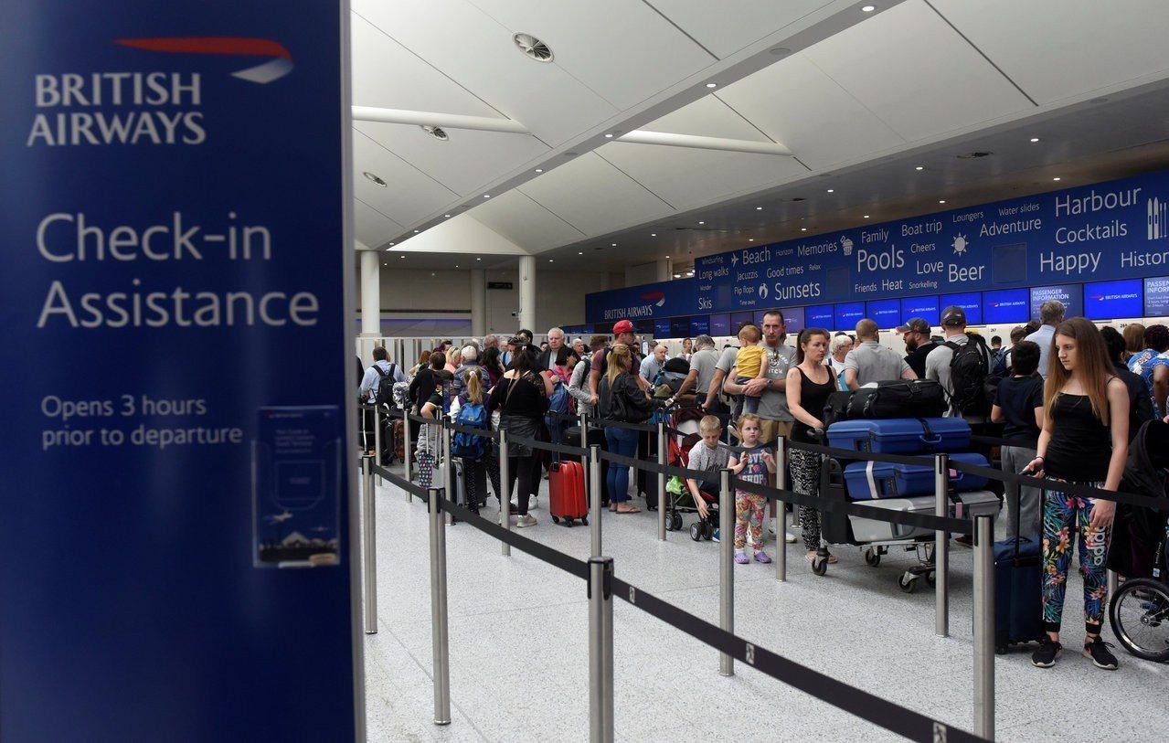 旅客在格域機場的英航報到櫃台前,排隊託運行李。(路透)