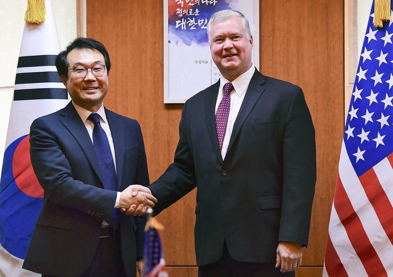 美國國務院北韓政策特別代表畢根(圖右)與南韓六方會談團長李度勳(圖左)握手。 歐...