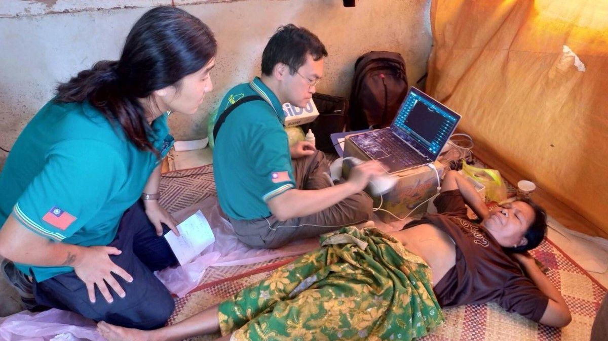 義大醫院醫學研究部長孫灼均在印尼荒島義診,以自備的儀器替民眾診療。圖/義守大學提...