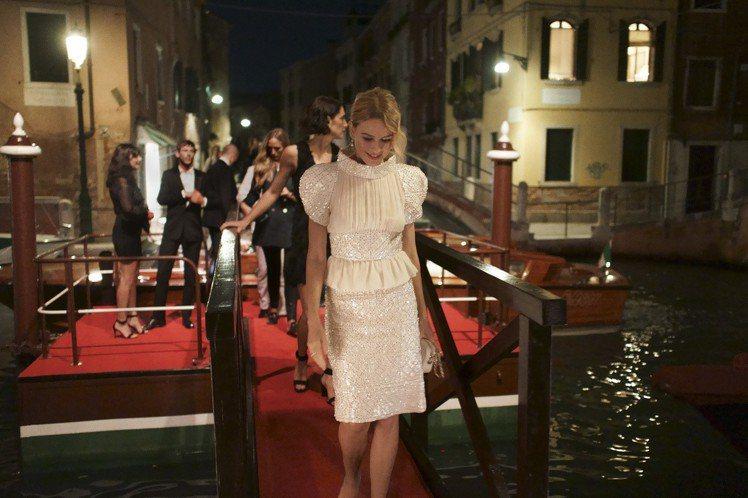 娜歐蜜華茲挑了2018/19 Cruise度假系列白色絲質上衣與同款裙子,搭配同...