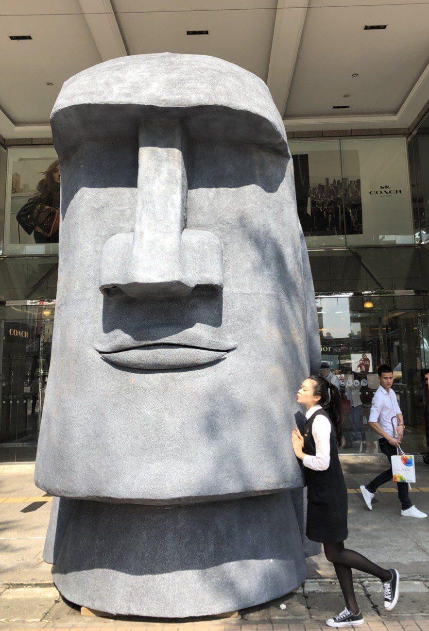 桃園遠百即日起在大門口擺放5公尺高的摩艾石像,吸引民眾爭相拍照。圖/桃園遠百提供