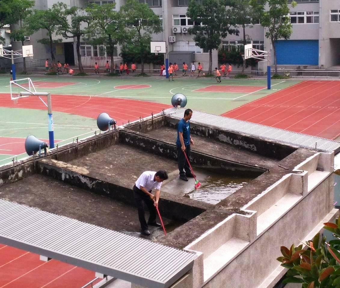 員林市大同國中校長謝國士(左)和工友洪朝朋(右)一起爬上升旗台打掃清淤,被偷拍後...