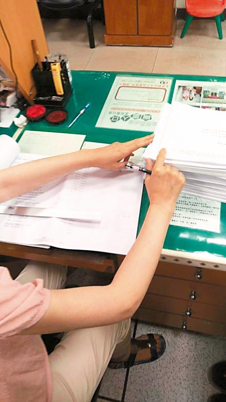 嘉義縣戶政所每位戶政人員桌上都擺滿一大疊待查對名冊,工作量遽增。 記者魯永明/攝...
