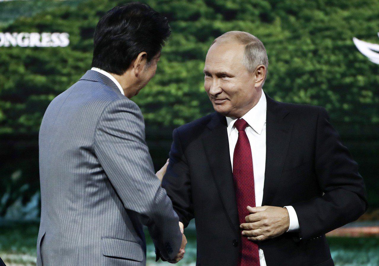 俄羅斯總統普亭(圖右)與日本首相安倍晉三(圖左)握手。 美聯社