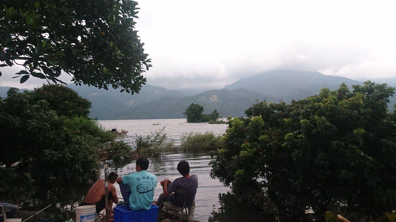 釣客邊垂釣邊欣賞湖光山色。圖/施忠志提供