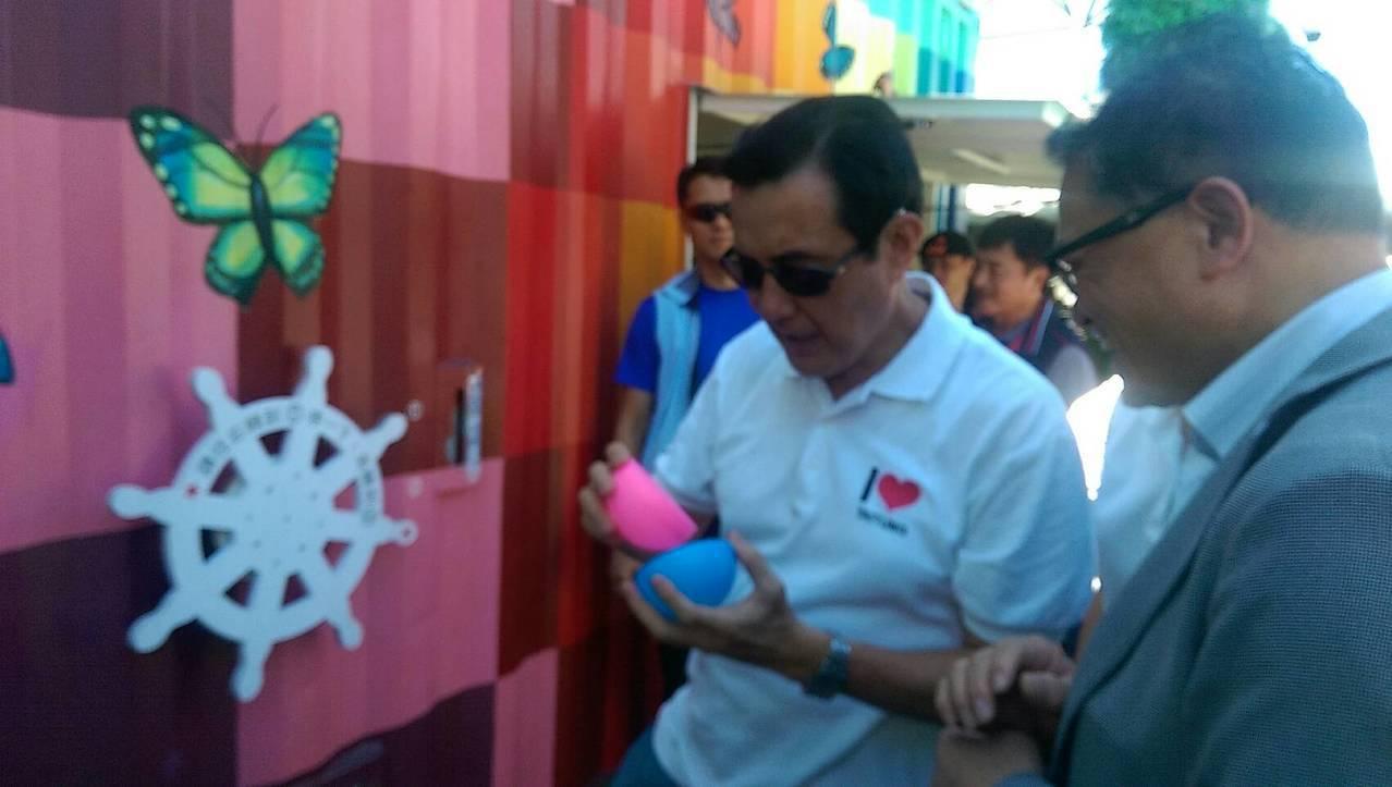 前總統馬英九好奇打開扭蛋球,裏頭寫道「不只時尚,還很有用」,兌換到手機充電線手環...