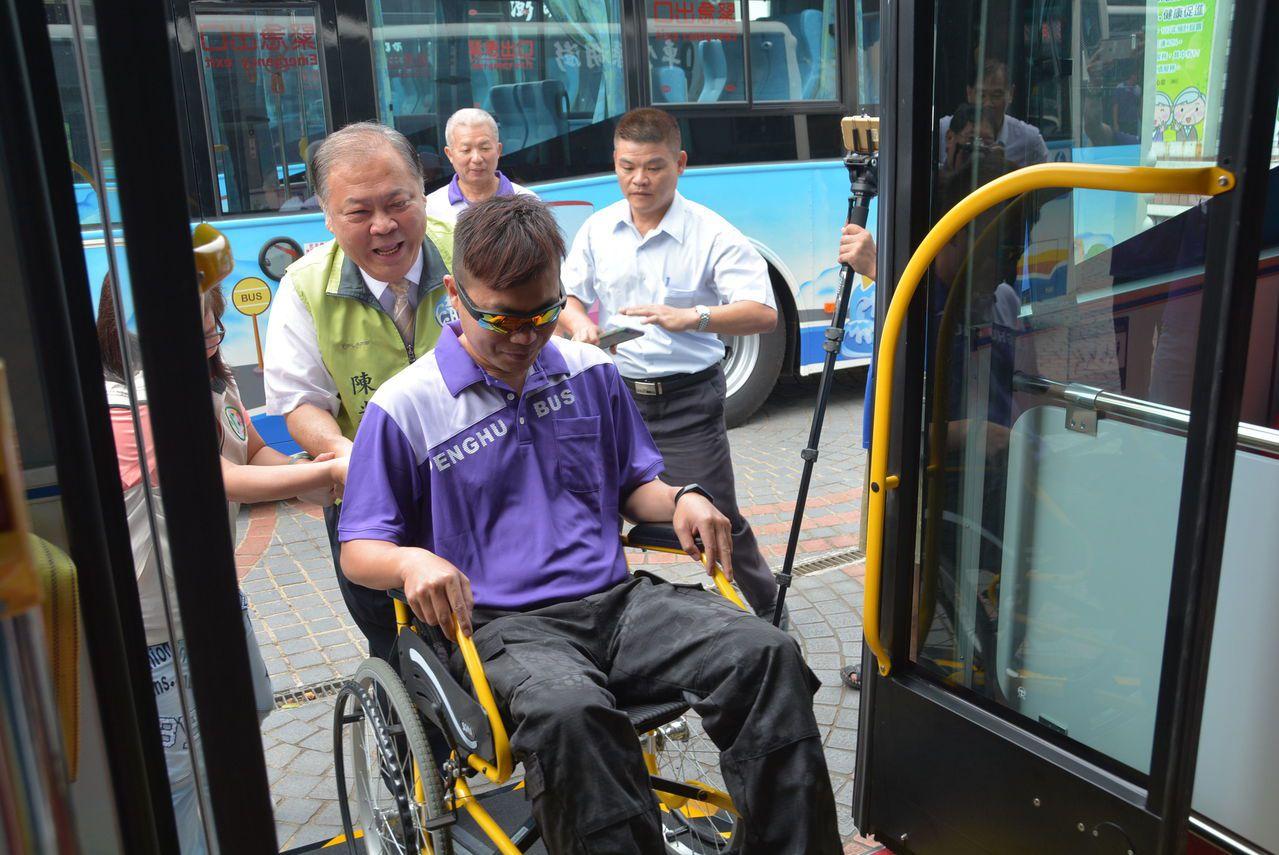 澎湖縣長陳光復(左)今天主持新公車啟用典禮,推著坐輪椅的民眾上公車。圖/澎湖縣政...