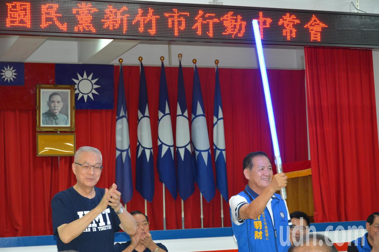 中國國民黨行動中常會今天下午移師新竹市,黨主席吳敦義(左)授一把藍色的「光劍」給...