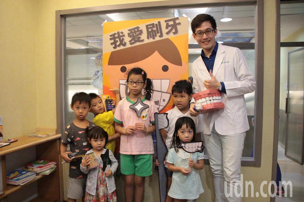 林口長庚紀念醫院兒童牙醫師張伯森拿著大牙齒道具和超大牙刷陪孩子刷牙,教導孩童正確...