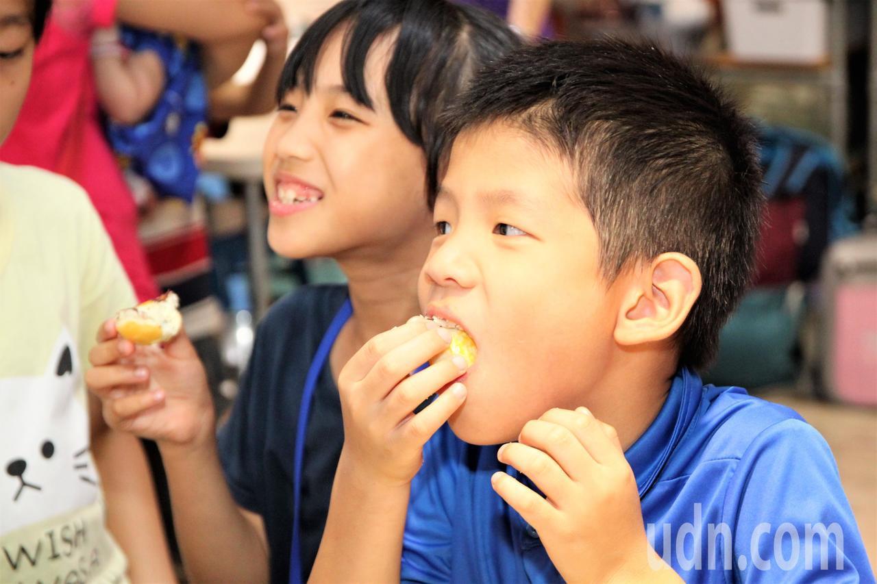 台中市太平國小的弱勢兒童吃著自己動手做出的月餅,都說「好香、好好吃喔!」。記者黃...