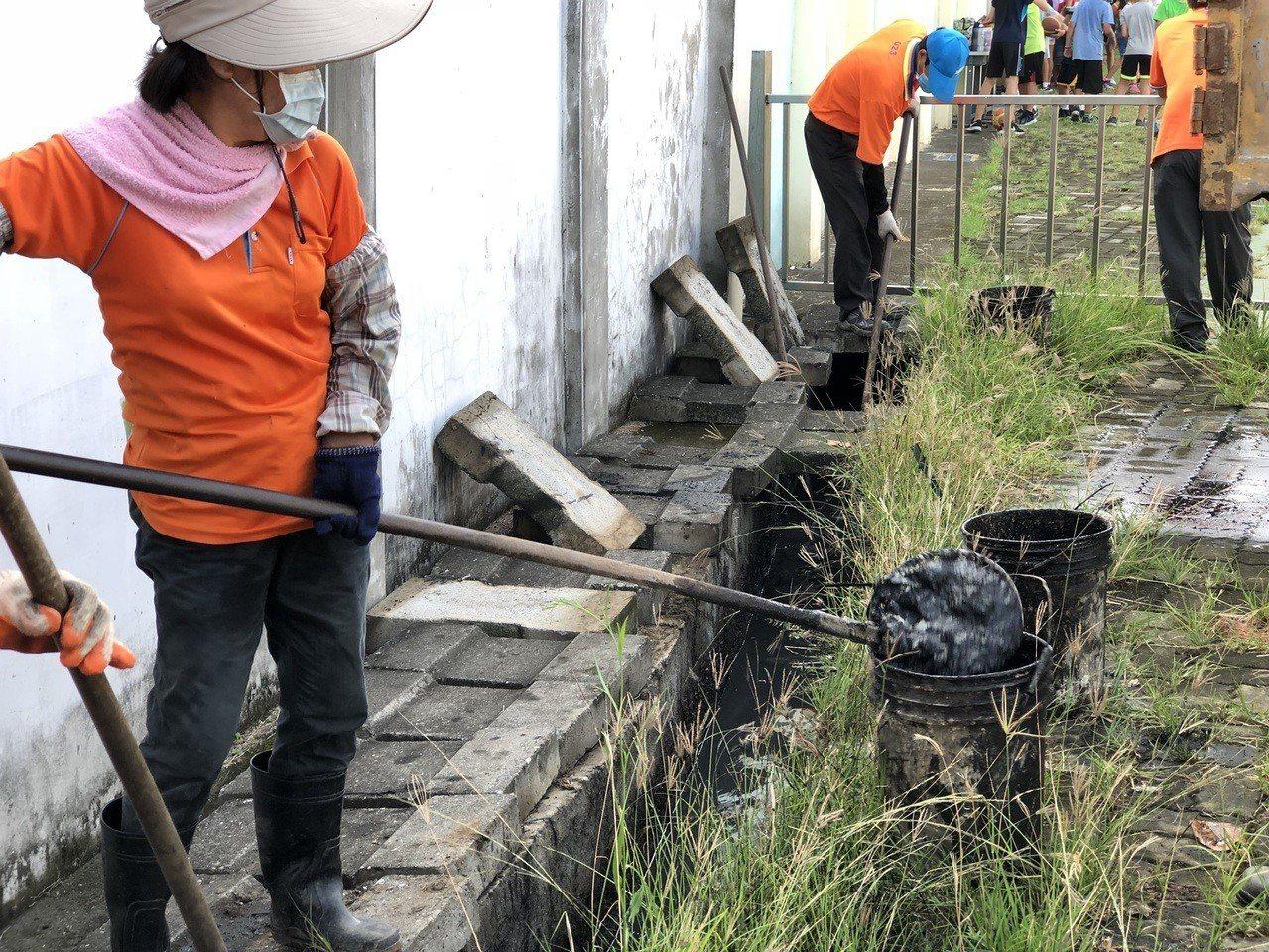 員林市清潔隊員今天到育英國小幫忙打開水溝的水泥蓋後進行清淤。記者何烱榮/攝影