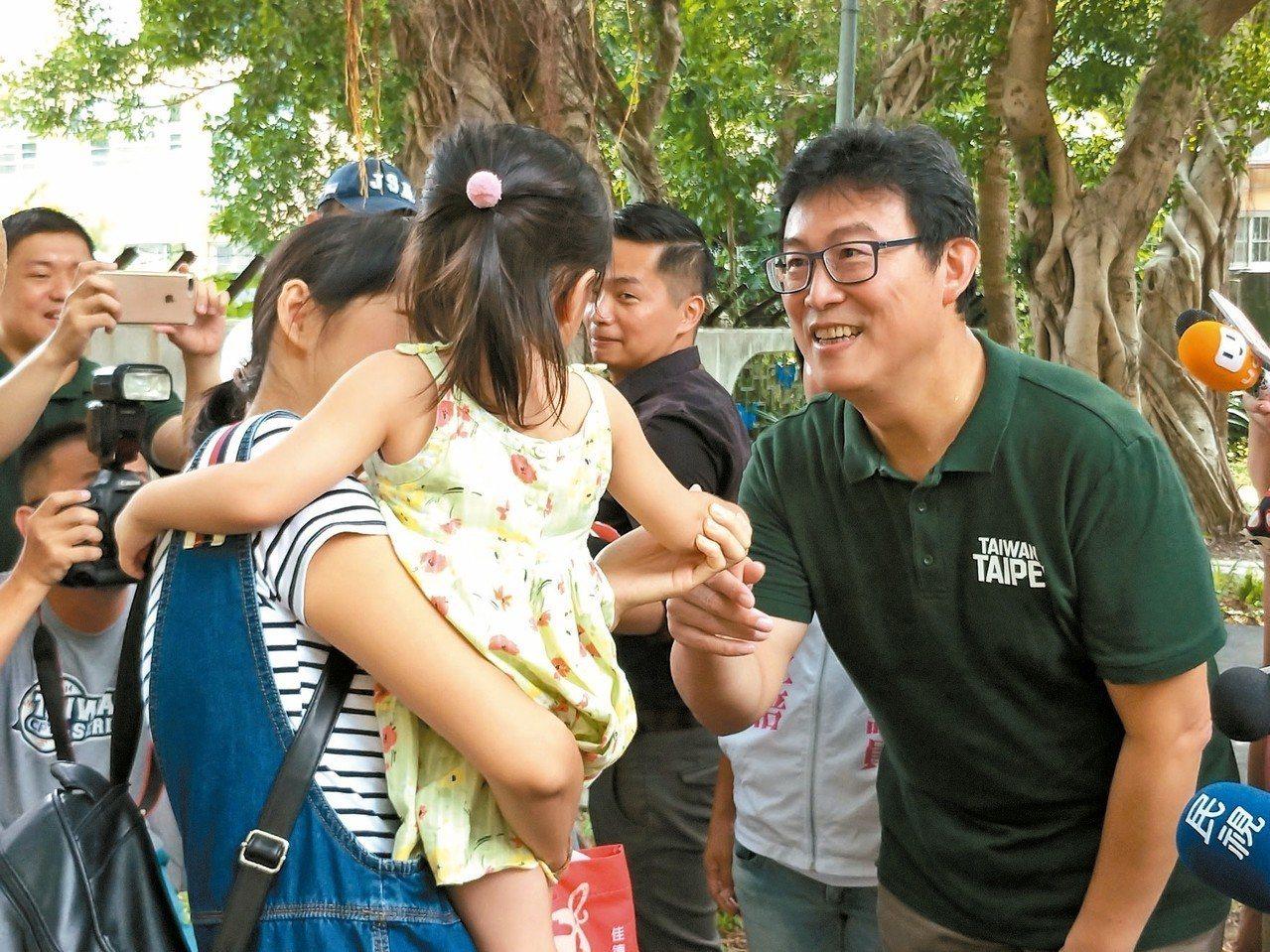 民進黨台北市長參選人姚文智(右)昨至三民公園拜票,並向民眾說明自己的育兒政見。 ...