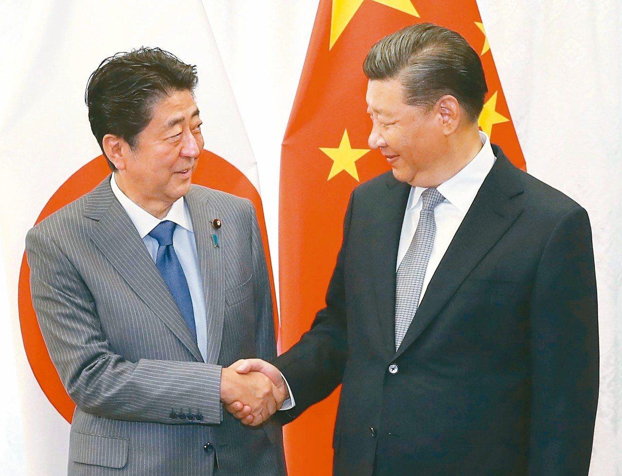 大陸國家主席習近平(右)昨在海參崴與日相安倍晉三會晤,兩人握手致意。 (法新社)