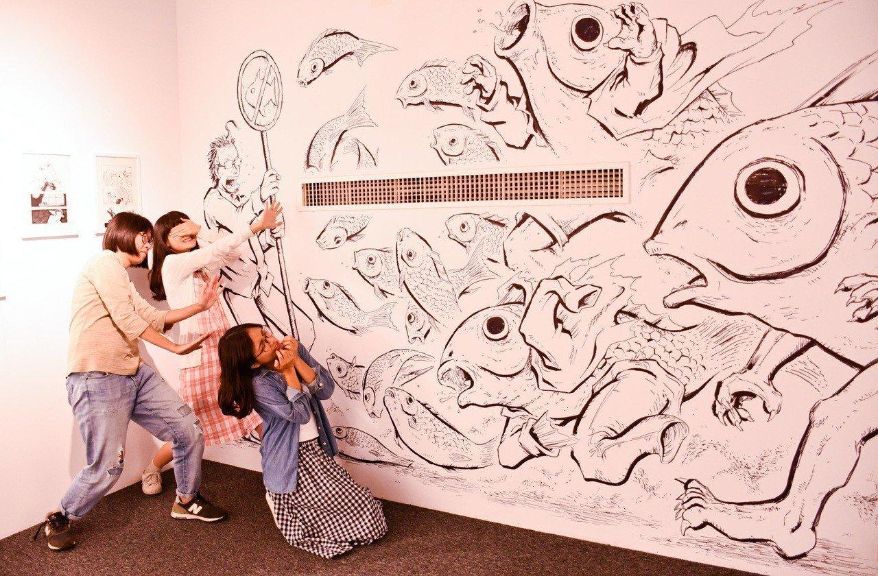 「怕魚的男人」漫畫家李隆杰現地創作壁畫宣揚魚的可怕,與民眾一起戰勝對魚的恐懼。記...