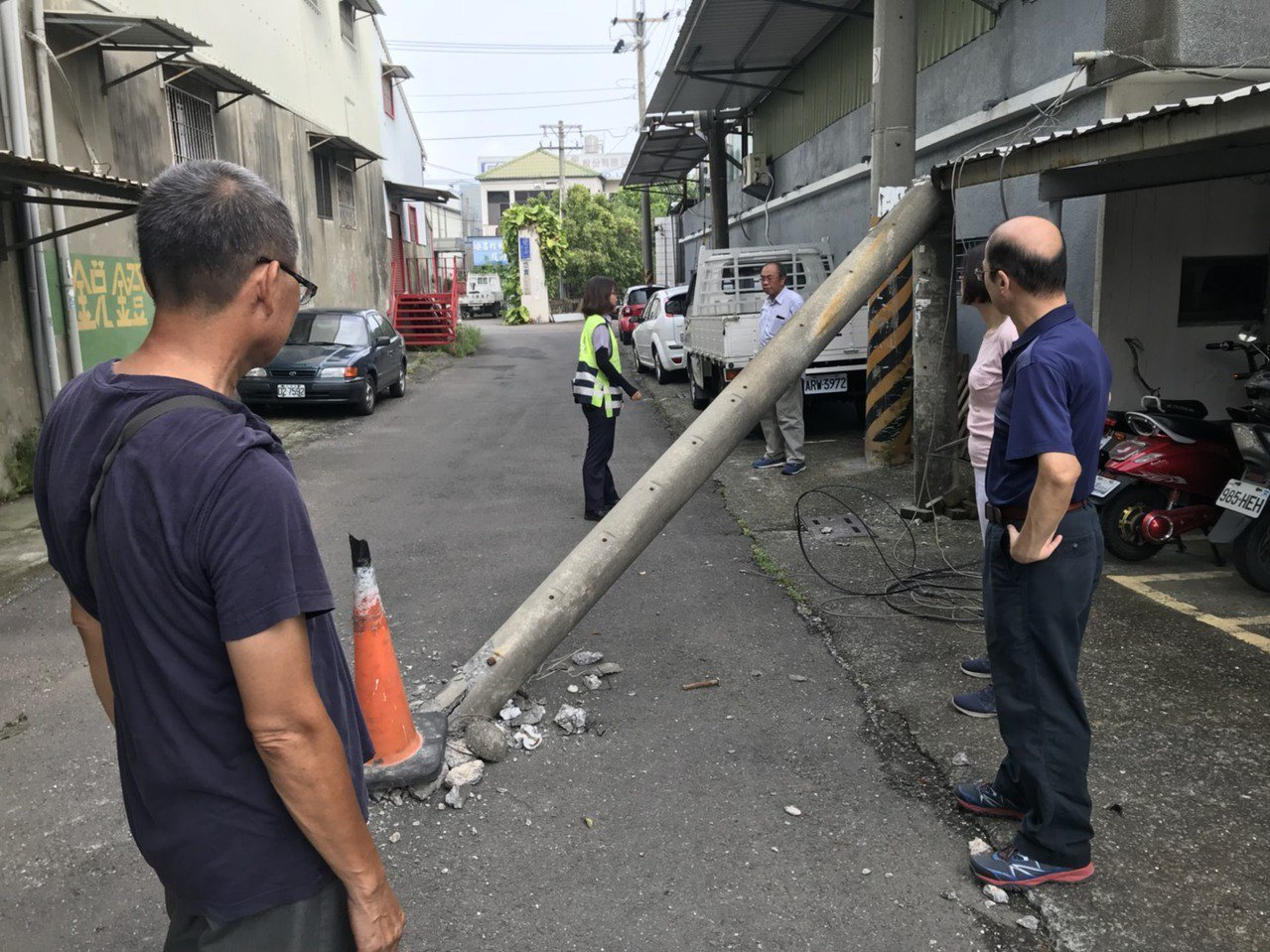 貨櫃車轉彎經過巷道時不小心拉到電線扯斷電桿, 電桿倒在路中央砸出一個洞。 記者周...