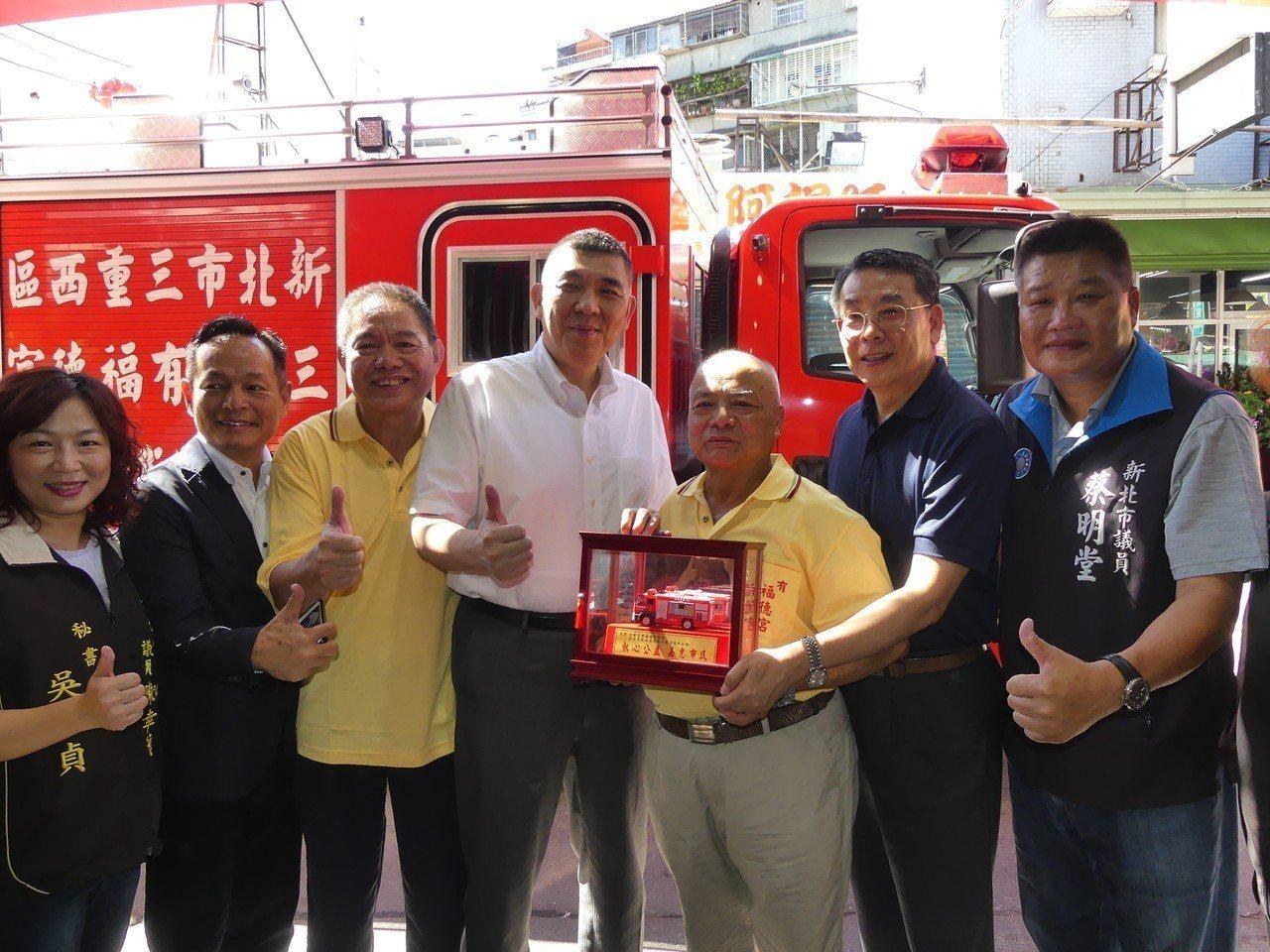 三重區三民街「大有福德宮」今天捐贈1輛水箱車給新北市消防局,局長黃德清(中)代表...