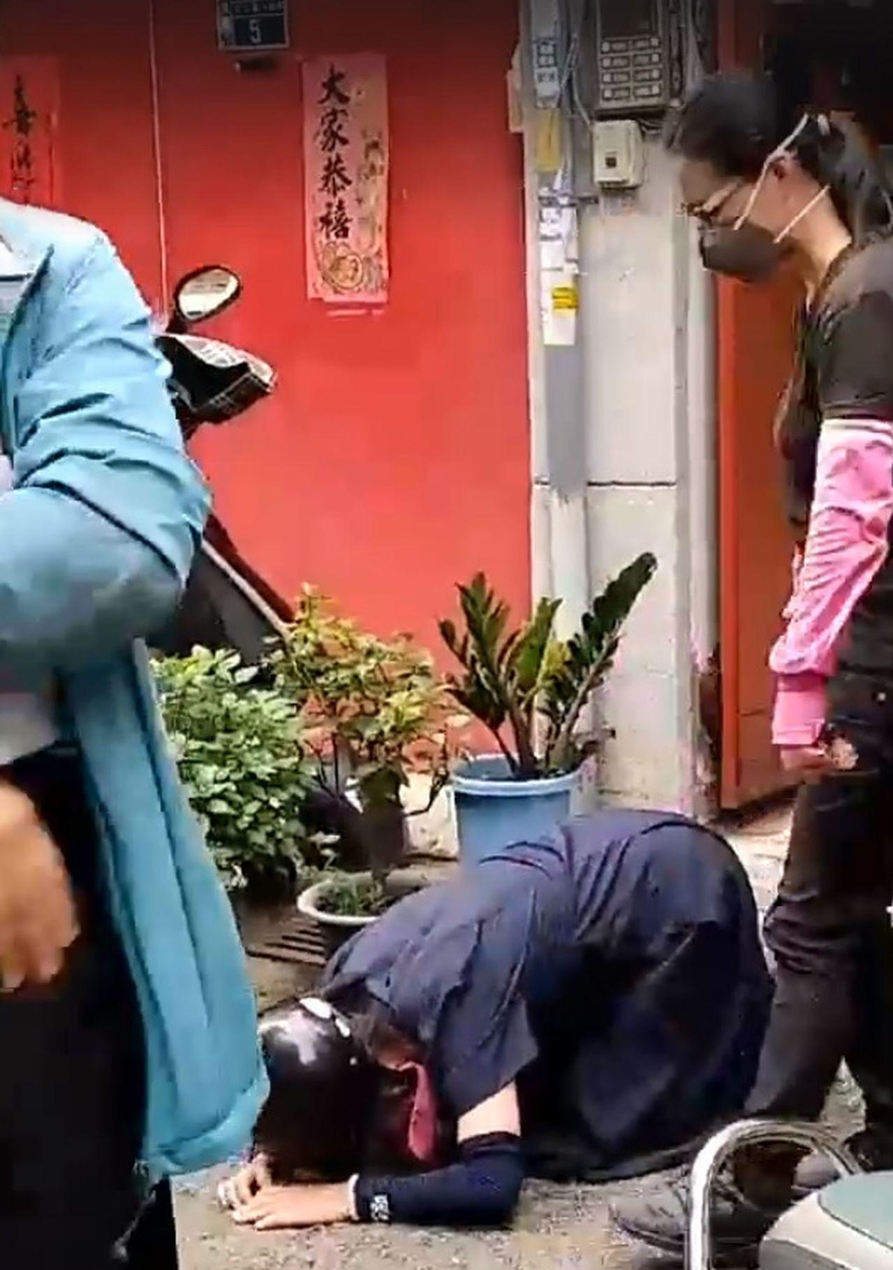 婦人拒絕防疫人員進屋噴藥,不惜下跪阻止。圖/翻攝臉書「台中市政府環境保護局工會」