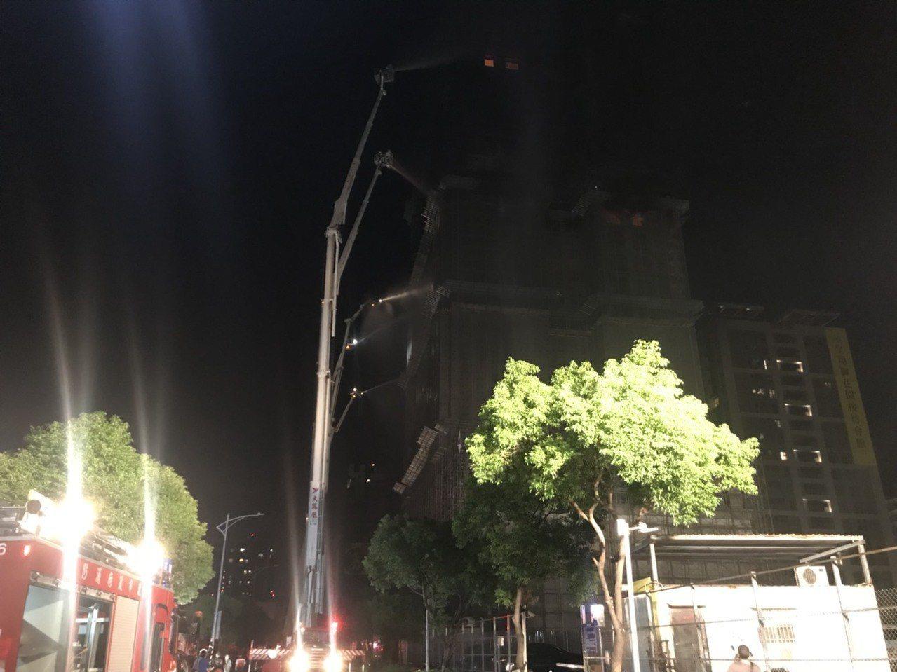 消防局以9部雲梯車分布在大樓外部噴灑,控制火勢。記者袁志豪/攝影