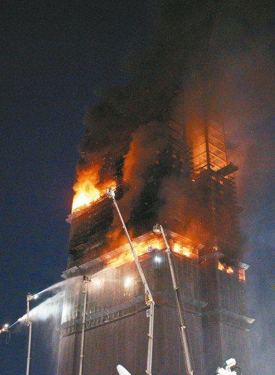 新北市新莊區一處24層樓工地昨晚不明原因起火,15樓以上全面燃燒,上午仍可見高樓...