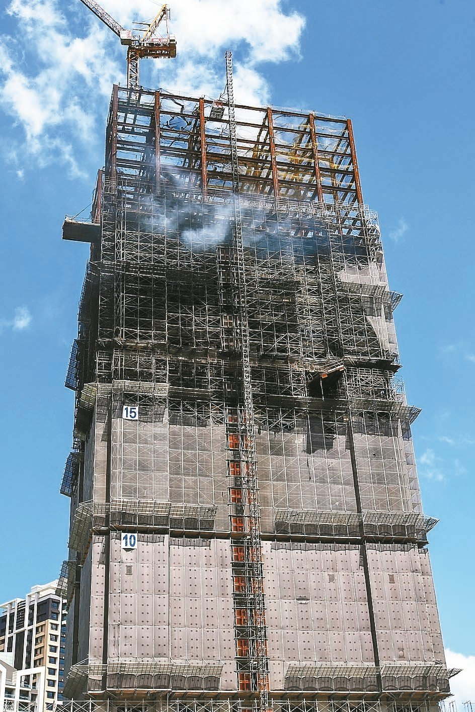 新北市新莊區一處24層樓工地燒了17小時,上午仍可見高樓層冒出白煙。 記者王騰毅...