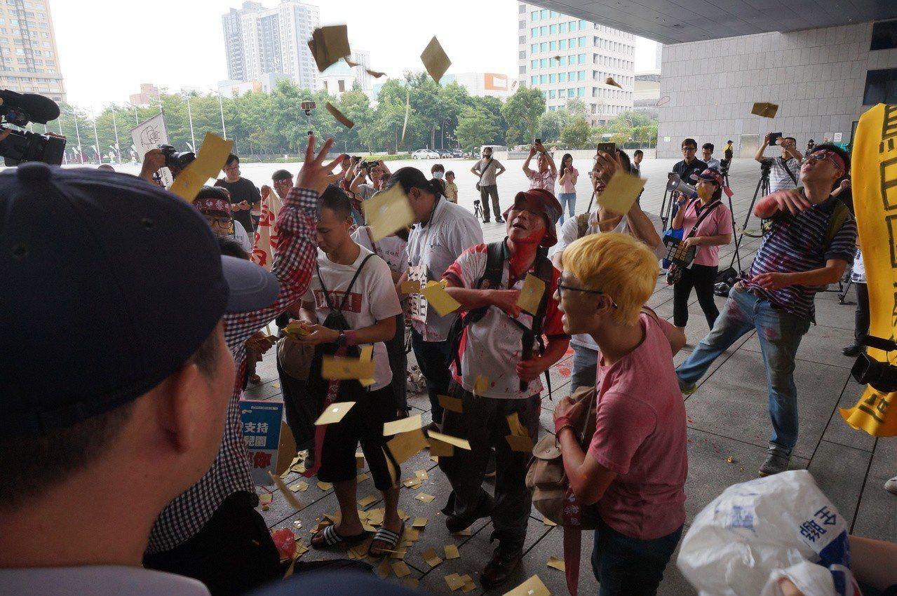 黎明幼兒園自救會今早到市府抗議,撒冥紙、潑紅漆,警方驅離時發生推擠。記者洪敬浤/...