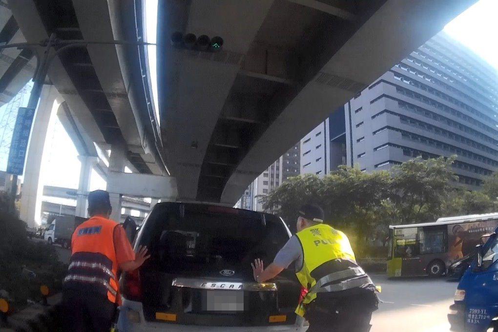 新莊警分局警員推車協助車輛拋錨的民眾。記者袁志豪/翻攝