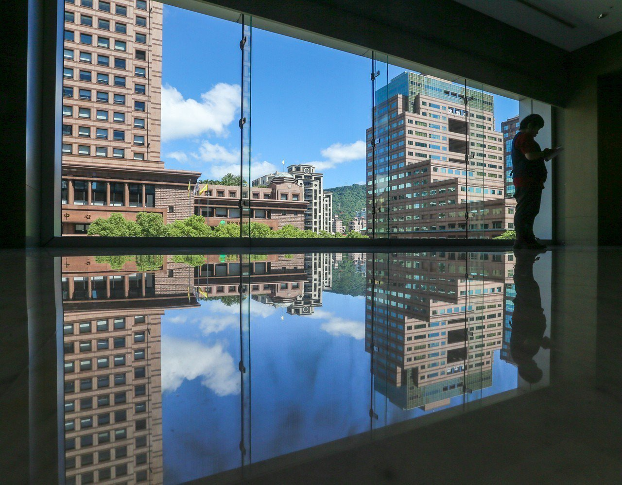昨天天氣晴朗炎熱穩定,藍天白雲透過玻璃帷幕映照在大樓地板上,形成秋日的特別景色。...