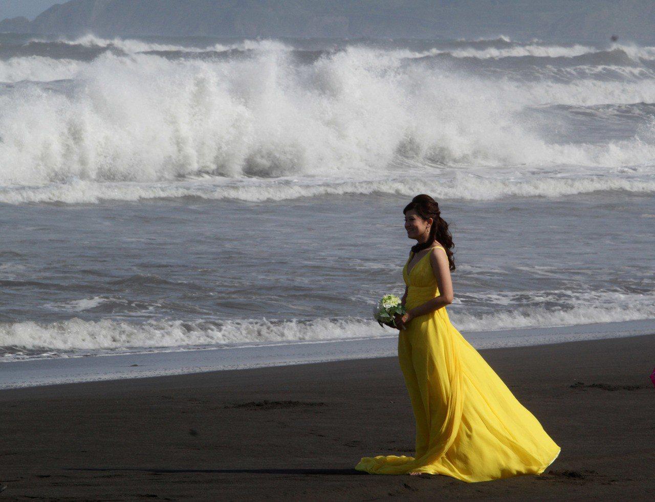 2012年中颱「天秤」來勢洶洶,宜蘭縣海邊出現長浪,卻仍有新人冒險到海邊拍結婚照...