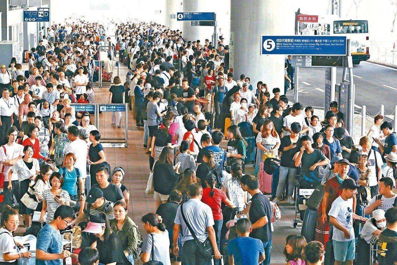 燕子颱風侵襲日本,關西機場跑道淹水導致關閉,約五千人受困,旅客在航廈外大排長龍等...