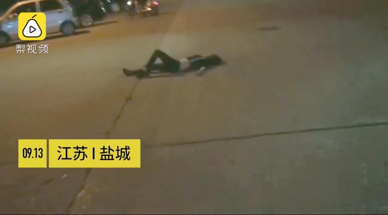 一名妙齡女子半夜躺在馬路中央。圖/截自《梨視頻》