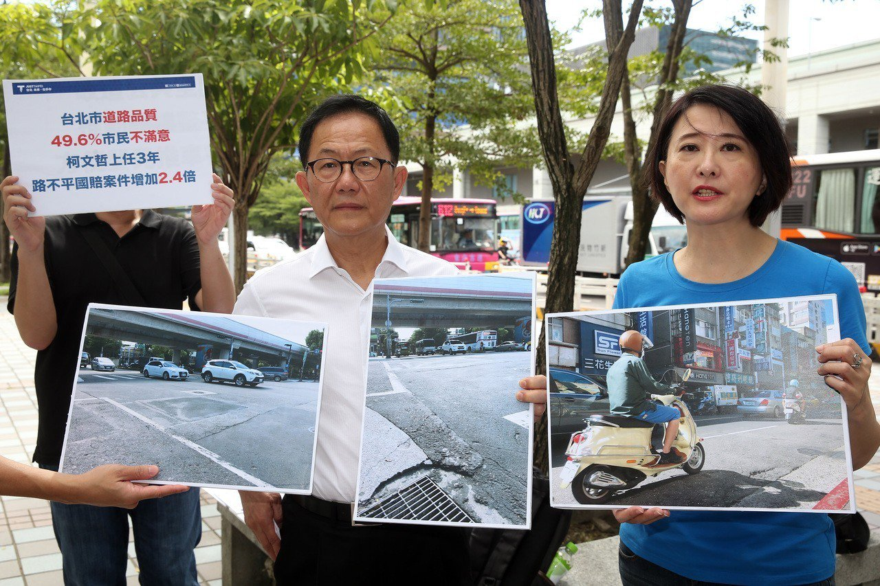 國民黨台北市長參選人丁守中(中)昨天和議員王鴻薇(右)舉行「路不平造成國賠案」記...