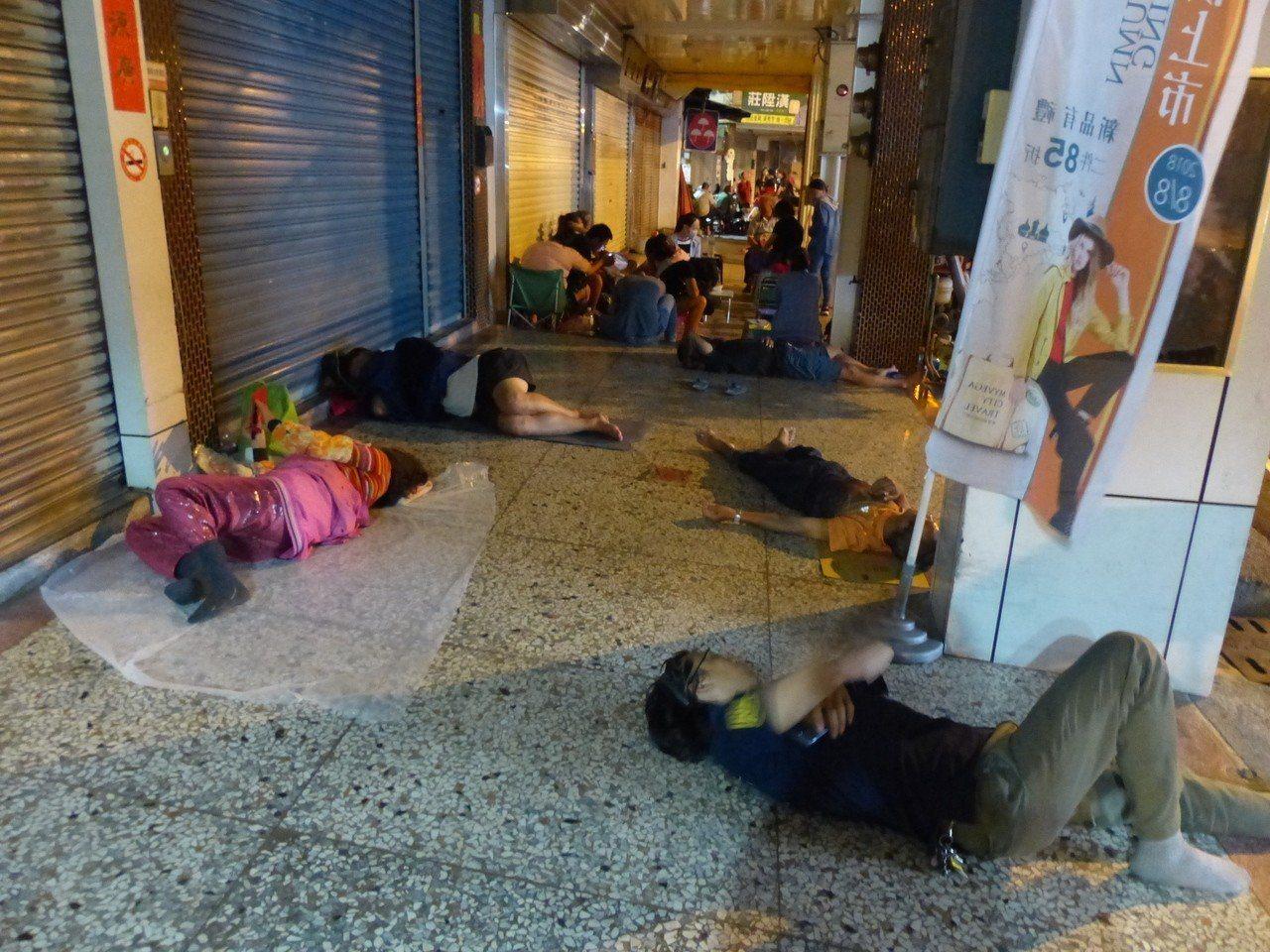 民眾排隊排累了,索性躺臥在騎樓呼呼大睡。記者劉明岩/攝影